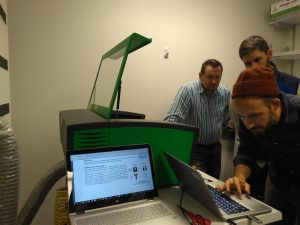 Three men stand around a table with a computer and a green laser cutter. Jeff is bent over the computer, while Scott and Bret look on with interest.